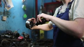 The concept of gender equality. Young pretty woman in work uniform, checking the bearing. Work in an auto repair shop. Hands close
