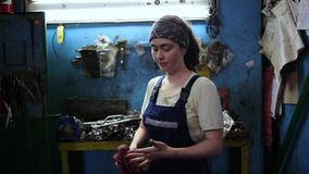 The concept of gender equality. A young pretty woman in a work uniform wipes her hands with a rag. Work in an auto repair shop