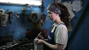 The concept of gender equality. Young pretty woman in work uniform, wiping tools with a rag. Work in an auto repair shop