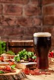 Concept of Georgian restaurant. Glass of black beer with foam stands on wooden table with beer snack stock image