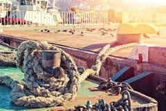 Concept geregelde levensstijl en permanente woonplaats - de meertroskabel houdt het schip in één plaats in de zeehaven op een zon stock foto