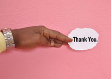 CONCEPT OF GESTUAL ACKNOWLEDGMENT. Close-up of hand holding a piece of paper on pink background on which is written Thank you as personalized concept of gestural Stock Photography
