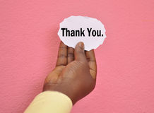 CONCEPT OF GESTUAL ACKNOWLEDGMENT. Close-up of hand holding a piece of paper on a pink background on which is written Thank you as a personalized thank you Royalty Free Stock Photo