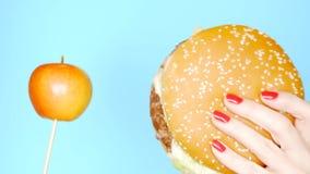 Concept gezond en ongezond voedsel Yaloko tegen hamburgers op een heldere blauwe achtergrond Vrouwelijke handen met rode spijker stock footage