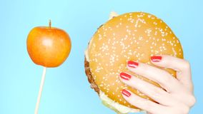 Concept gezond en ongezond voedsel Yaloko tegen hamburgers op een heldere blauwe achtergrond Vrouwelijke handen met rode spijker royalty-vrije stock foto