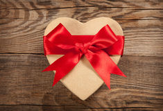 Concept gift. Box in the form of heart on the old boards royalty free stock image