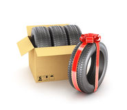 Concept of gift. The car tires in the cardboard box and one tire in gift ribbon stock photography