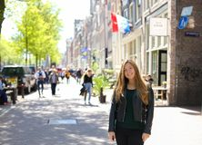 Concept of girl with Netherlands flag in background. Concept of female tourist and cheap tours to Europe stock photography