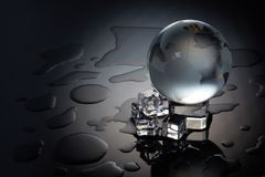 Concept of global warming. Globe and melting ice cube on a dark background with water drops. Concept of global warming. Protecting environment stock photography