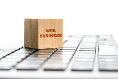 Concept of globalization and online business. Wooden cube with a Web business sign sitting on computer keyboard. Conceptual of modern globalization and online Royalty Free Stock Image
