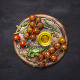 Concept of good nutrition, cherry tomatoes on a branch, rosemary, oil on a round cutting board wooden rustic background top vie Stock Photos