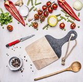 Concept of good nutrition, various vegetables, spices and oil with a cutting board, a knife vegetables and wooden spoon place Stock Photos