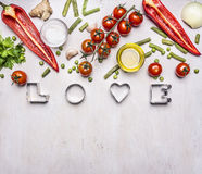 Concept of good nutrition, various vegetables, spices and oil, with the word Love border ,place for text  on wooden rustic backgro Stock Images