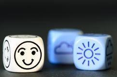 Concept of good  summer weather - emoticon and weather dice on b. Lack background - stock photo Royalty Free Stock Image