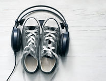 Concept with gray sneakers and black headphones laid Stock Photos
