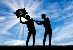 Concept of greed and selfishness. Silhouette of a man trying to take from another man a piggy bank with money Royalty Free Stock Images