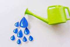 Concept green watering pot and and water droplets made of paper on a white background. Close up Concept green watering pot and and water droplets made of paper Stock Images