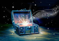Concept greeting card of opened chest treasure with mystical mir. Acle light on wooden background, beautiful art design, close up royalty free stock images