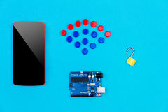 Concept. `hacked`. Top view of smartphone, microchips, microcontroller and unlock lock on blue background with wifi symbol from colorful hardware buttons Royalty Free Stock Photography