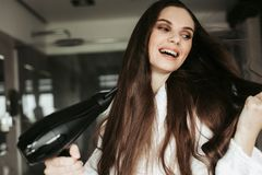 Young cheerful woman drying hair with blowdryer stock photography