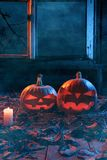 The concept of Halloween. Two luminous evil scary pumpkins, jack. Lantern, with candles, leaves and eerie branches outside the window with a warm and cold blue stock photos