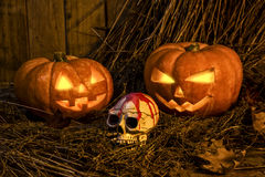 Concept Halloween. Two spooky pumpkins with candles. Focus of the skull Stock Images