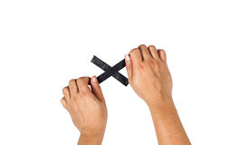The concept of hands is about to taped to a black cross. Royalty Free Stock Image