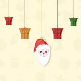 Concept of hanging gift box and santa face. Hanging colorful gift boxes and Santa Claus face on beige background for Christmas and other occasion Stock Photography