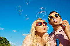 Concept of happiness, cheerful, fun, love. Happy couple in sunglasses hearts having fun blowing soap bubbles against the blue sky. royalty free stock photography