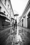 Happy, loving couple kissing under an umbrella on a city street on a rainy day Royalty Free Stock Photos