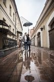 Happy, loving couple kissing under an umbrella on a city street on a rainy day Stock Photos