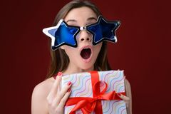 Concept of happiness when receiving presents on Christmas. Portr. Ait of happy surprised crazy woman with open mouth. She is wearing big funny sunglasses and Stock Photography