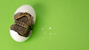 Concept happy birthday new home. Souvenir toy building in a broken egg on a green background. White eggshell with a golden gift royalty free stock photos