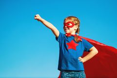 Concept happy child superhero hero in red cloak  in nature royalty free stock photo