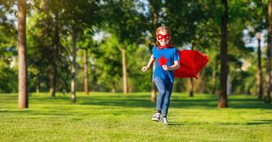 Concept happy child superhero hero in red cloak  in nature. Concept happy child superhero hero in red cloak at sunset in nature royalty free stock photos