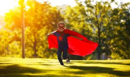 Concept happy child superhero hero in red cloak  in nature royalty free stock image