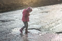 Concept - happy childhood. Little girl plays in puddle, children`s fun, dirty and wet shoes, life in the village, sunlight stock photo