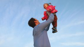 Concept of happy family. Dad throws baby up high against sky. Dad plays with his little daughter in the park. dad threw stock video