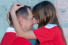 Concept of happy father day. Daughter hugs dad. Dad and daughter in red. Concept of happy father day royalty free stock photos