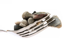 Concept about hard digestion. Fork with stones Stock Photos