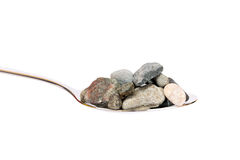 Concept about hard digestion. Spoon with stones Royalty Free Stock Photos