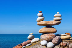 Concept of harmony and balance. Balance and poise stones against the sea. Rock zen in the form of scales.  royalty free stock image