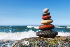 Concept of harmony and balance. Beautiful pyramid of colorful wet pebbles . Rock Zen in the background of the sea Stock Photography