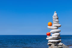 Concept of harmony and balance. Rock Zen with apple and  orange Royalty Free Stock Photography
