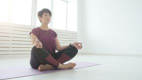 Concept of harmony, sport and health. Middle-aged Woman doing yoga in a white interior. Concept of harmony, sport and health. Woman doing yoga in a white stock video