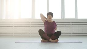 Concept of harmony, sport and health. Middle-aged Woman doing yoga in a white interior. Concept of harmony, sport and health. Woman doing yoga in a white stock footage