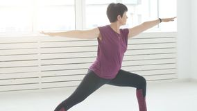 Concept of harmony, sport and health. Middle-aged Woman doing yoga in a white interior. Concept of harmony, sport and health. Woman doing yoga in a white stock video footage