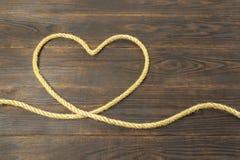 Concept hart van de jutekabels, liefde, kader voor groetkaart op bruine houten achtergrond stock foto
