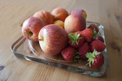 Apples, peaches and strawberries on on glass serving plate on the wooden table close up. Concept of harvest. New apples season. Concept of autumn. Concept of stock image