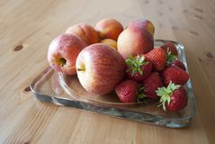 Apples, peaches and strawberries on on glass serving plate on the wooden table close up. Concept of harvest. New apples season. Concept of autumn. Concept of royalty free stock photo
